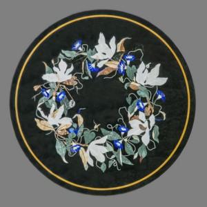 """Table ronde """"Lys"""" en marqueterie de pierres dures. Décor tiré d'un modèle ancien. Plateau noir avec fleurs blanches et bleus en lapis-lazuli. Pierres vertes: baroda et hard green"""