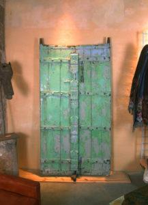 Ancienne porte indienne avec son palimpseste de couches de peinture. Une superposition de couleurs qui lui confèrent une allure de tableau contemporain.