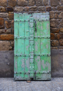 Ancienne porte indienne avec son palimpseste de couches de peinture. Une superposition de couleurs (vert et gris violet) qui lui confèrent une allure de tableau contemporain.