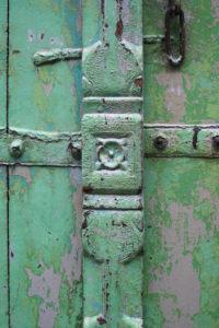 Ancienne porte indienne avec son palimpseste de couches de peinture. Une superposition de couleurs qui lui confèrent une allure de tableau contemporain. Détail des sculpture et de l'aspect de la surface