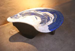 Lapislazuli et travertin pour ce plateau posé sur un piétement en tôle de fer qui reprend également le mouvement de la